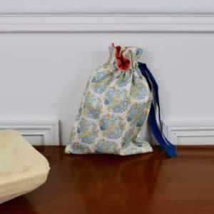 Pochon taille petite en Tilda Flower Nest Blue, intérieur rouge, ruban bleu