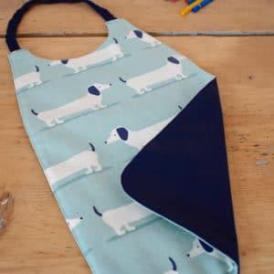 Serviette enfant en coton imprimé chiens blancs et bleus sur fond vert, coton uni bleu marine, tour de cou bleu marine